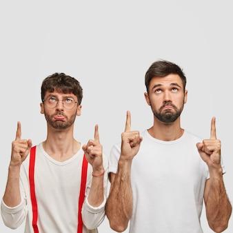 Foto van sombere mannen met donker haar, gekleed in witte kleren, naar boven gericht, met ontevreden gezichtsuitdrukkingen