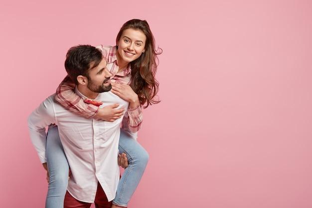 Foto van speelse man geeft op de rug rit naar vriendin