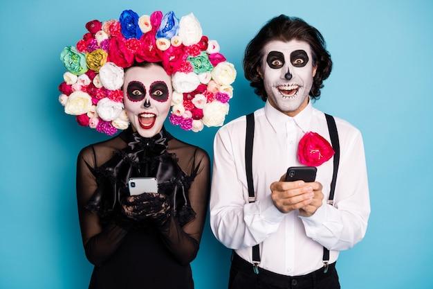 Foto van spookachtig demonenpaar man dame houd telefoons opgewonden vind manier word spoken grap vriend draag zwarte jurk dood kostuum rozen hoofdband bretels geïsoleerde blauwe kleur achtergrond