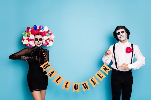 Foto van spookachtig eng twee mensen man dame houdt lint direct vinger evenement promotie draag zwarte korte mini-jurk dood kostuum rozen hoofdband bretels geïsoleerde blauwe kleur achtergrond
