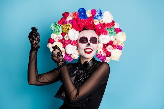 Foto van spookachtig monster ondode schepsel dame grappige latin dans doen alsof hebben maracas exotisch land carnaval dragen zwarte kanten jurk dood kostuum rozen hoofdband geïsoleerde blauwe kleur achtergrond