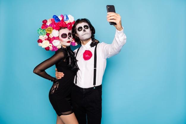 Foto van spookachtig monster paar man dame omarmen vasthouden telefoon maken thema selfie foto draag korte mini zwarte jurk dood kostuum rozen hoofdband bretels geïsoleerde blauwe kleur achtergrond
