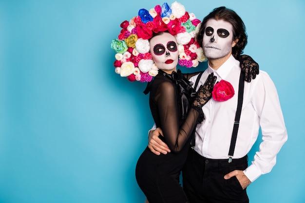 Foto van spookachtig teder paar man dame meisje knuffelen wachten festival voertuig vervoer dode mensen dragen alleen zwarte jurk dood kostuum rozen hoofdband bretels geïsoleerde blauwe kleur achtergrond