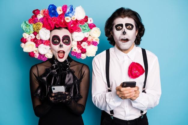 Foto van spookachtige demon twee mensen man dame houd telefoons staren monster wezens verboden schandaal dragen zwarte jurk dood kostuum rozen hoofdband bretels geïsoleerde blauwe kleur achtergrond