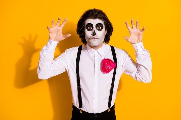 Foto van spookachtige geest ondode borstelige man steekt handen op griezelig gebaar staren grappige grimas angstaanjagende make-up dragen wit overhemd roos dood kostuum bretels geïsoleerde gele kleur achtergrond