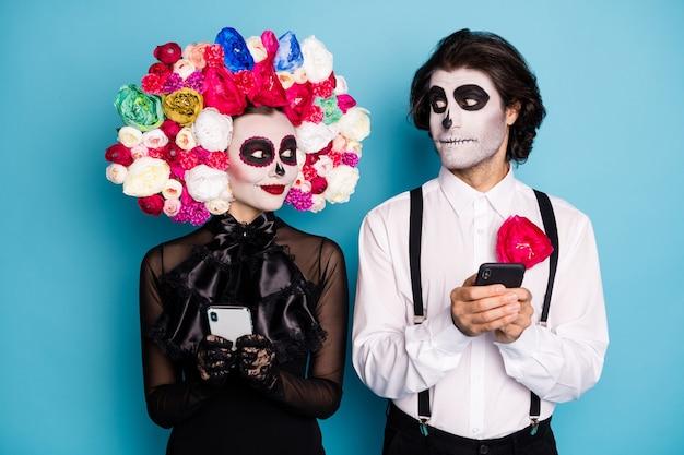 Foto van spookachtige twee mensen man dame houd telefoon kijk oog uitgenodigd groep monster chat draag zwarte jurk dood kostuum suiker schedel rozen hoofdband bretels geïsoleerde blauwe kleur achtergrond