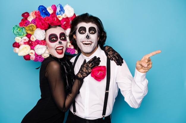 Foto van spookachtige twee mensen man dame knuffelen directe vinger lege ruimte verbaasd festival begin promo dragen zwarte jurk dood kostuum rozen hoofdband bretels geïsoleerde blauwe kleur achtergrond
