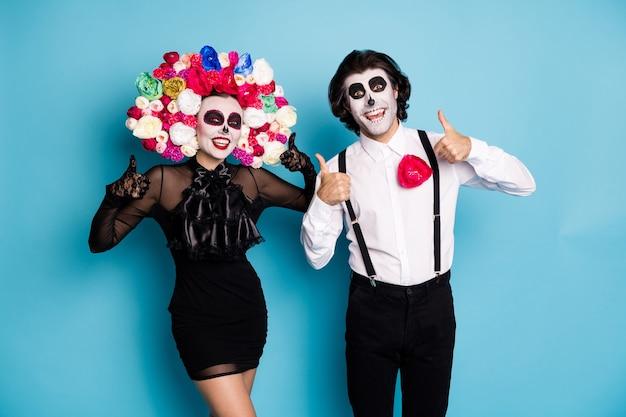 Foto van spookachtige twee mensen man dame show duim omhoog keuren ondoden lokale taverne carnavalskleding zwarte korte mini jurk dood kostuum roos hoofdband bretels geïsoleerde blauwe kleur achtergrond