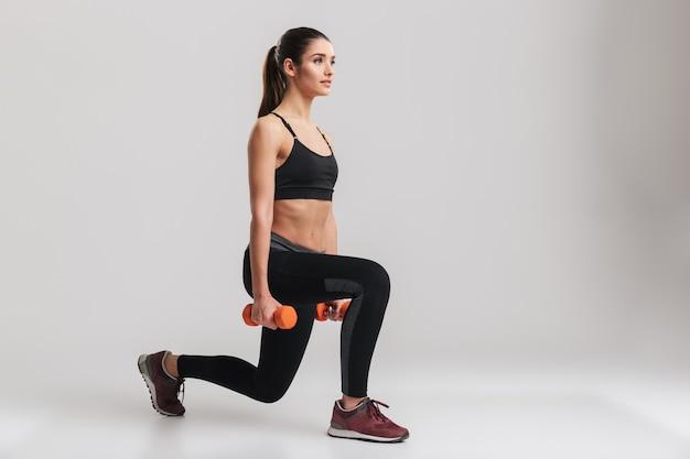 Foto van sportieve blanke vrouw gehurkt met kleine gewichten, geïsoleerd over grijze muur