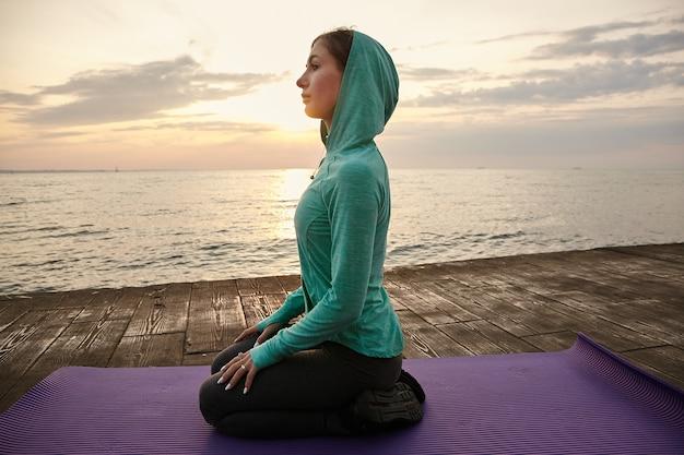 Foto van sportieve jonge vrouw in yoga pose, gekleed in lichte sportkleding, treinen aan zee, rustgevend en mediteren.