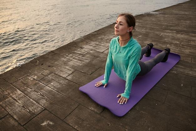 Foto van sportieve jongedame in lichte sport draagt, maakt ochtend die zich uitstrekt in yoga pose, treinen aan zee