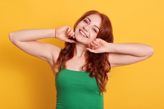 Foto van sterk roodharige vrouw met groene casual t-shirt, geeft aan op gele muur, glimlachend rechtstreeks in de camera kijken