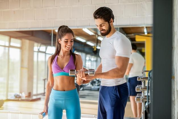 Foto van sterke glimlachende persoonlijke fitnesstrainer die zijn schattige vrouwelijke cliënt helpt met zware gewichten trainen in de sportschool.
