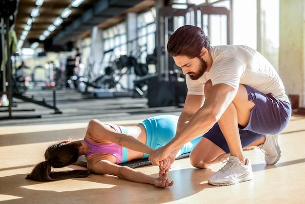 Foto van sterke knappe persoonlijke fitnesstrainer die zijn vrouwelijke cliënt helpt om haar spieren te strekken na de training.
