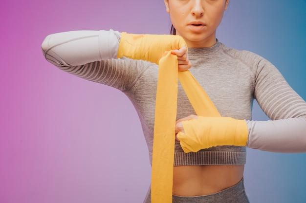 Foto van sterke sportvrouw inwikkeling handen met boksen wraps vóór de strijd
