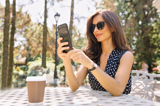 Foto van stijl vrouw met mooi haar en charmante glimlach zit in de zomercafetaria in zonlicht met haar telefoon en werkt.
