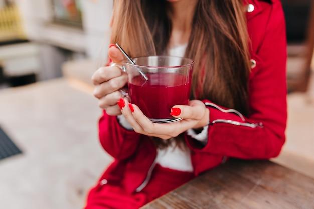Foto van stijlvolle blanke vrouw met kopje thee op voorgrond