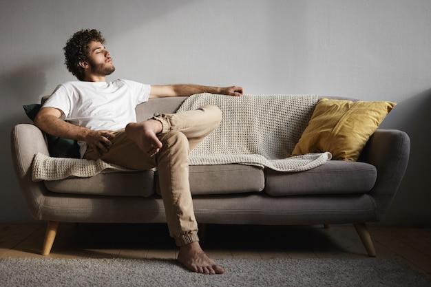 Foto van stijlvolle knappe jonge kerel met pluizige baard, volumineus kapsel en blote voeten met gesloten ogen, in slaap vallen of luisteren naar klassieke muziek, genieten van vrije tijd, zittend op de bank