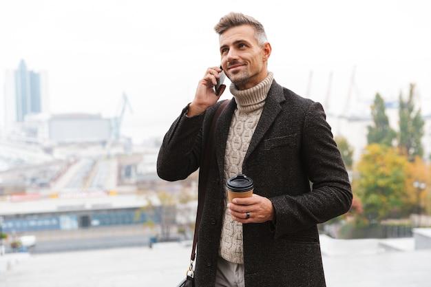 Foto van stijlvolle man 30s dragen jas praten op mobiele telefoon en afhaalmaaltijden koffie te houden, tijdens een wandeling door de stad straat