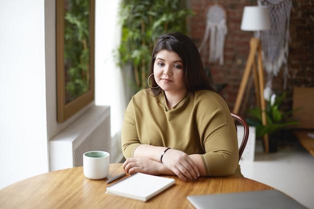 Foto van stijlvolle overgewicht jonge vrouwelijke ontwerper zittend op een naaiatelier en koffie drinken, nadenken over concept van nieuw project, schetsen in dagboek, nadenkend doordachte blik hebben