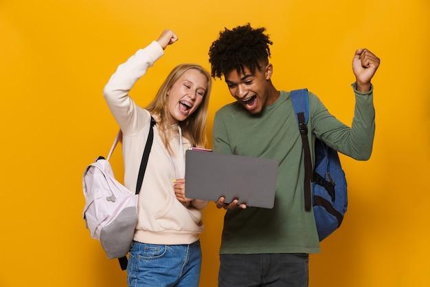 Foto van stijlvolle studenten man en vrouw 16-18 die rugzakken dragen met zilveren laptop en oefenboeken, geïsoleerd op gele achtergrond