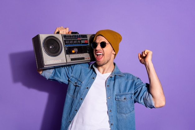 Foto van stijlvolle trendy vrolijke extatische schreeuwen muziekliefhebber dansen met luide bas recorder met handen geïsoleerd over paarse levendige kleuren achtergrond