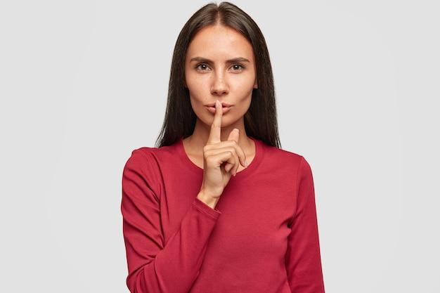 Foto van stille mooie brunette dame gekleed in rode trui, wijsvinger op de lippen houdt, heeft ernstige uitdrukking,