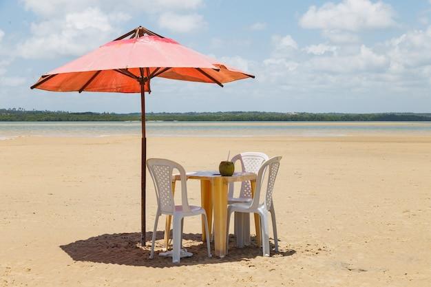 Foto van stoelen en paraplu met een vijver op de achtergrond. strand, vakanties en zomer