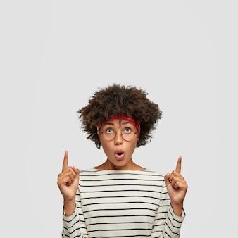 Foto van stomverbaasd meisje met donkere huid en afro-kapsel, houdt mond rond