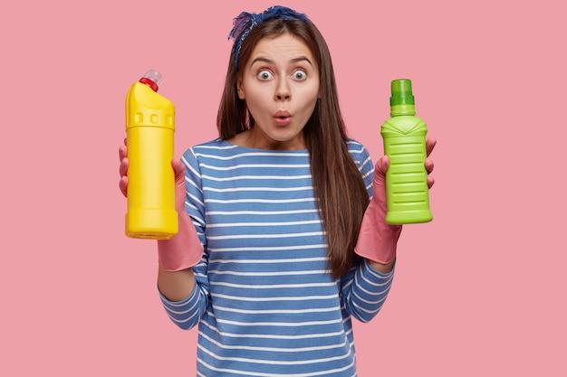 Foto van stomverbaasde blanke vrouw van schoonmaakdienst, draagt de noodzakelijke benodigdheden, draagt rubberen handschoenen, gekleed in een gestreepte trui
