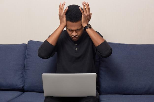 Foto van stressvolle overwerkte man met donkere huid heeft vreselijke migraine, terloops gekleed, werkt op laptopcomputer, probeert het werk af te maken