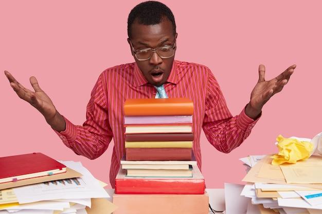 Foto van student kijkt stomverbaasd naar stapel boeken, weet niet wat te beginnen