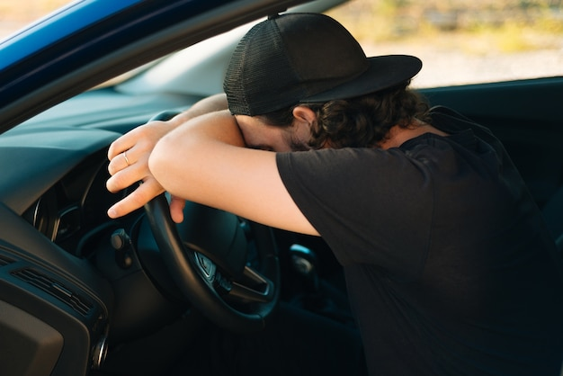 Foto van stuurprogramma man slapen op stuur in zijn auto