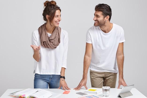 Foto van succesvolle marketingexperts komen samen om de belangrijkste kwesties van het werk te bespreken, modieuze kleding te dragen, gelukkig naar elkaar te kijken, model in de buurt van desktop met noodzakelijke dingen, geïsoleerd op wit