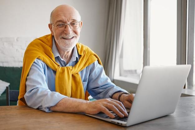 Foto van succesvolle positieve bejaarde bebaarde europese reisblogger artikel typen op draagbare computer, kijken en glimlachen stijlvolle trui dragen rond nek over blauw shirt