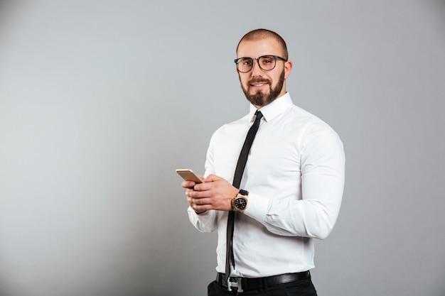 Foto van succesvolle volwassen man in glazen en stropdas communiceren met smartphone in handen, geïsoleerd over grijze muur