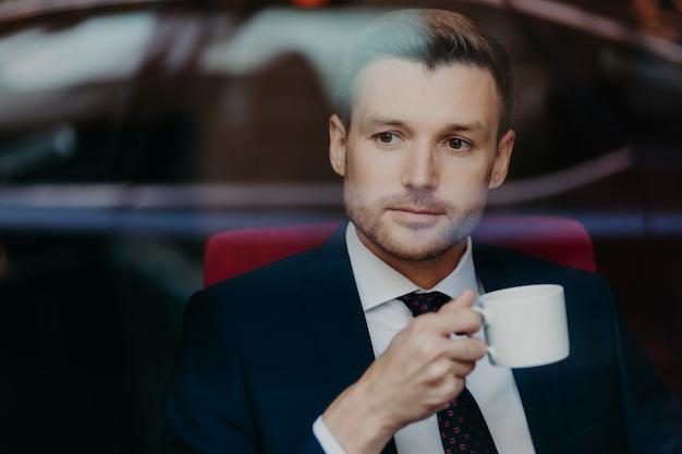 Foto van succesvolle welvarende mannelijke ondernemer met stoppels, draagt formele kleding