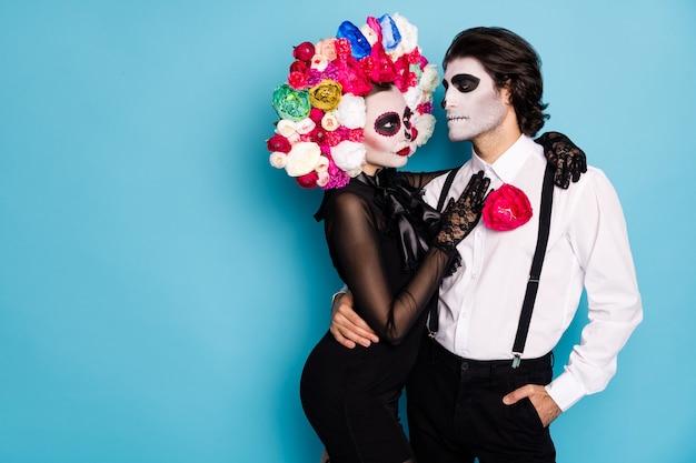 Foto van teder griezelig paar man dame knuffelen flirterige stemming woning eenzaam donker gotisch herenhuis dragen zwarte jurk dood kostuum rozen hoofdband bretels geïsoleerde blauwe kleur achtergrond