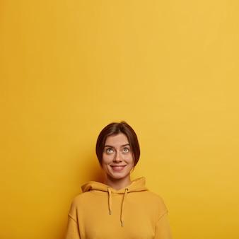 Foto van tedere mooie jonge vrouw gekleed in casual sweatshirt, kijkt boven met belangstelling, glimlacht zachtjes