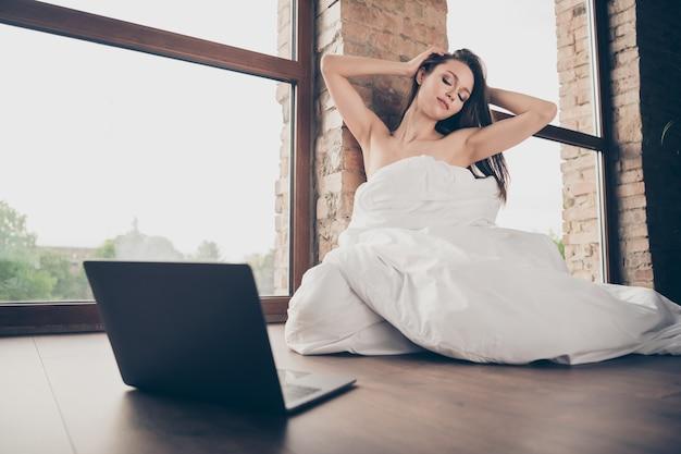 Foto van tedere verleidelijke dame quarantaine thuis blijven bedekt witte deken naakte schouders sensueel notitieboekje uitkleden vriendje videogesprek aanraken hoofd kapsel plagen zit vloer binnenshuis