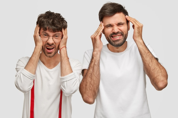 Foto van teleurgestelde mannen met vreselijke hoofdpijn, handen op de slapen, fronsende gezichten, ontevredenheid en overwerkt, vrijetijdskleding dragen, geïsoleerd over een witte muur. negatieve emoties