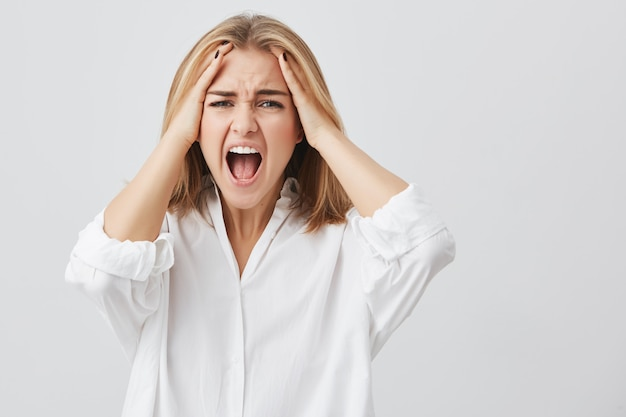Foto van teleurgestelde vrouw met blond haar die haar handen op tempels houdt fronsend gezicht met wijd geopende mond schreeuwend van wanhoop en angst.