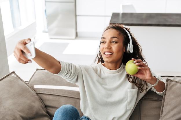 Foto van tevreden afrikaanse amerikaanse vrouw die hoofdtelefoons draagt die selfie op celtelefoon neemt, zittend op bank in licht appartement