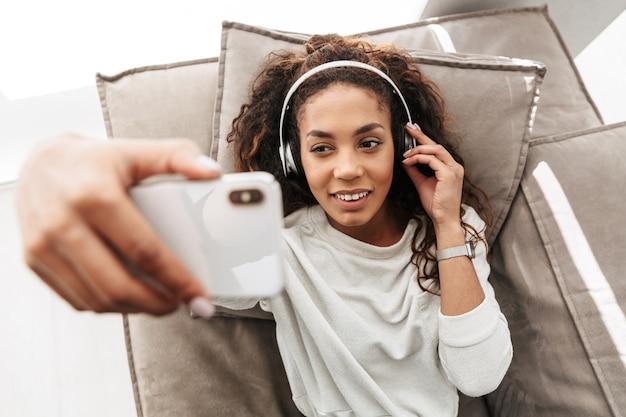 Foto van tevreden afrikaanse amerikaanse vrouw die hoofdtelefoons draagt die selfie op mobiele telefoon neemt, terwijl liggend op bank in licht appartement
