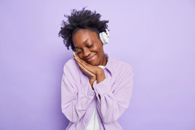 Foto van tevreden afro-amerikaanse vrouw met donkere huid sluit ogen houdt handpalmen tegen elkaar gedrukt kantelt hoofd herinnert zich iets