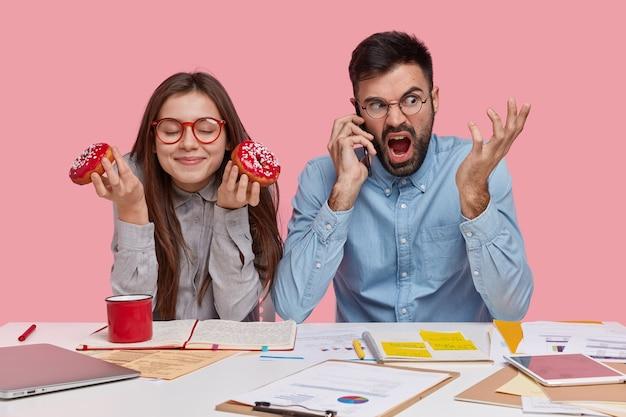 Foto van tevreden dame draagt bril met rode rand, eet heerlijke donuts, zit in de buurt van haar mannelijke partner die via slimme telefoon met boze uitdrukking spreekt