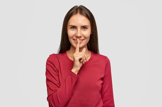 Foto van tevreden donkerbruine vrouw in rode kleren