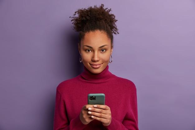 Foto van tevreden donkerhuidige duizendjarige meisje houdt mobiele telefoon, wacht op oproep, sms't met vriend in online chat, gebruikt speciale applicatie, tikt op smartphonescherm, controleert newsfeed, bladert op internet