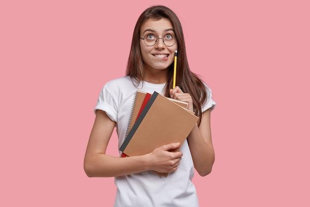 Foto van tevreden europese jonge dame kijkt gelukkig naar boven, houdt potlood, schoolboeken vast, heeft dromerige uitdrukking, schrijft notities