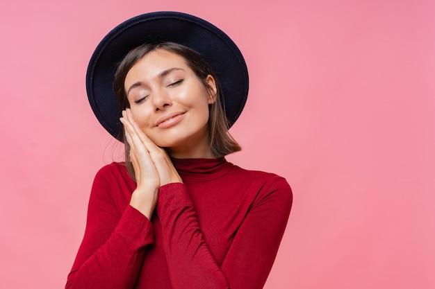 Foto van tevreden europese jonge vrouw met aangename brede glimlach, houdt de ogen gesloten, droomt over iets aangenaams, gekleed in een losse pullover, geïsoleerd.